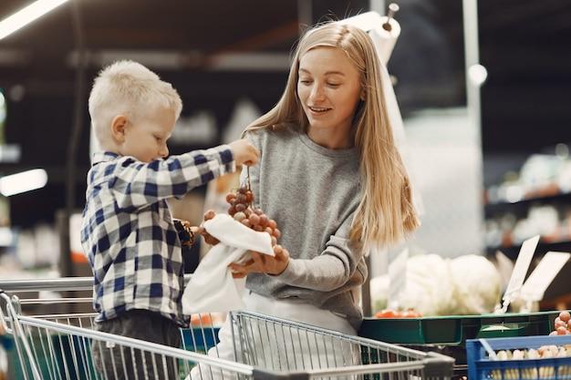 식료품을 사는 가족. 회색 스웨터에 어머니.