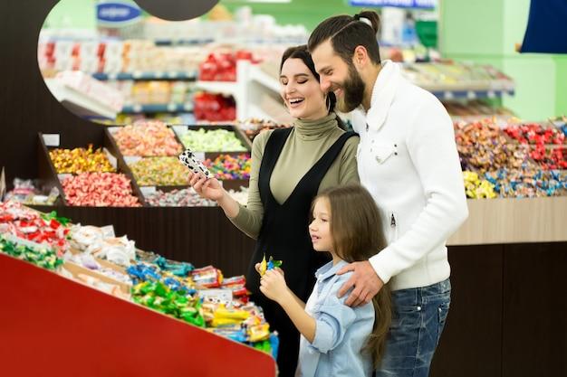 Семья покупает сладости в супермаркете