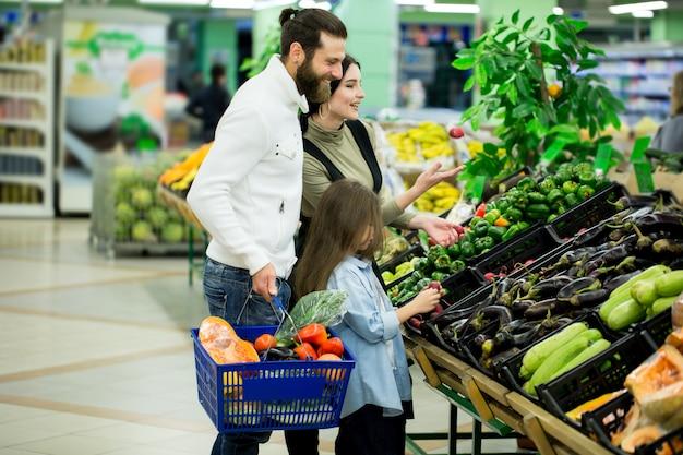 Семья покупает овощи в супермаркете