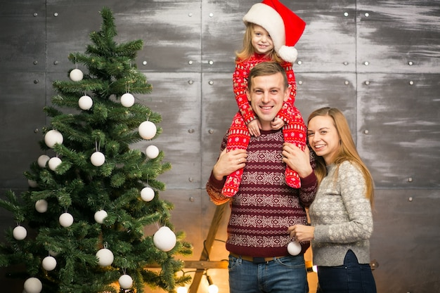 Family by the christmas tree with little daughter in a red hat