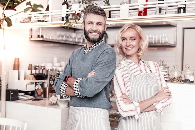 Семейное кафе. радостная милая пара стоит на кухне, открывая собственное кафе