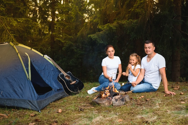 Family camping and cooking in campfire