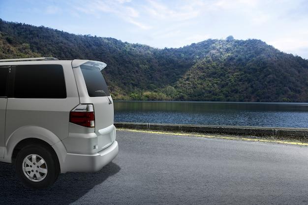 Семейный автомобиль на дороге с озером и долиной