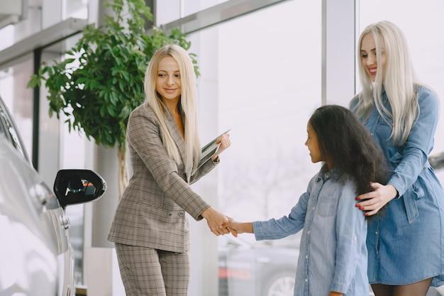 Famiglia in un salone di automobile. donna che compra l'auto. bambina africana con mther. manager con i clienti.