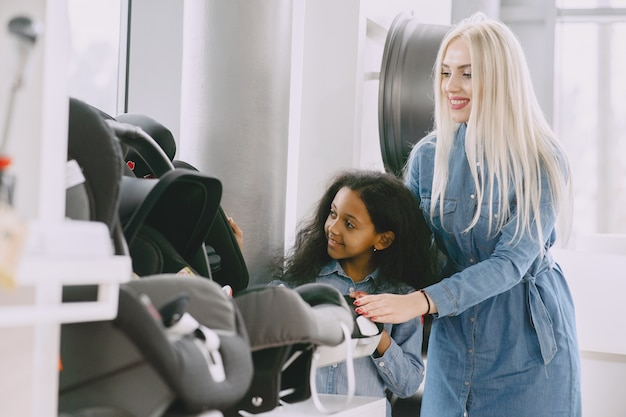 Family in a car salon. woman buying thecar seat. little african girl with mther.