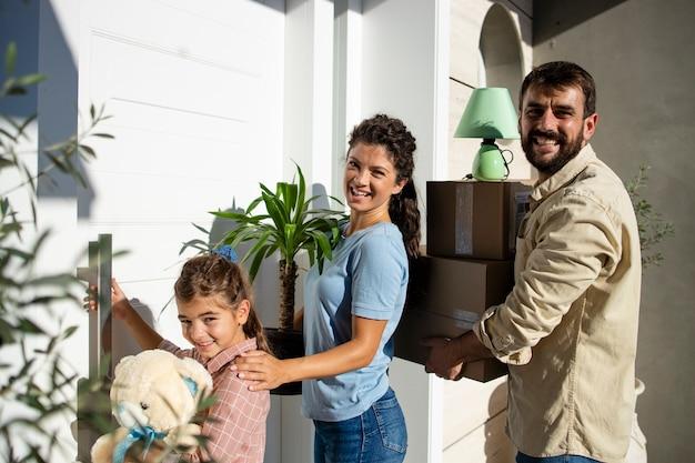 현관문을 통해 새 집에 들어가는 동안 상자와 꽃을 들고 가족