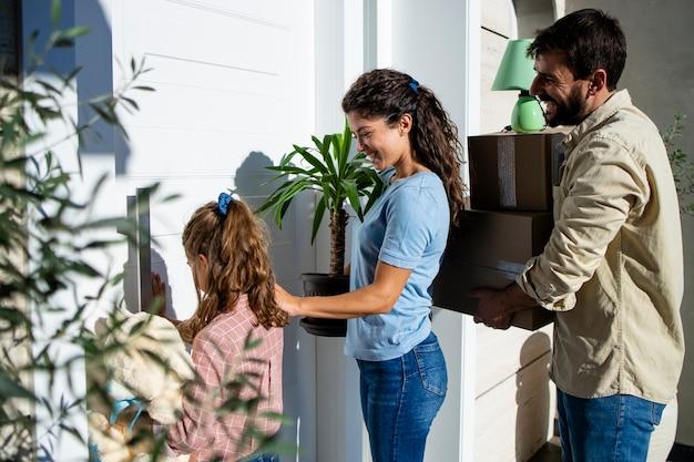 정문을 통해 새 집에 들어가는 동안 판지 상자와 꽃을 들고 있는 가족