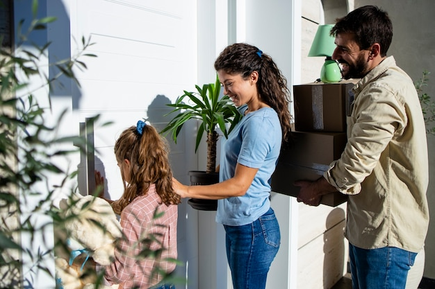 Family carrying cardboard boxes and flowers while entering their new house through the front door