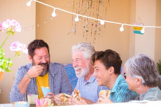 혼합 된 세대와 나이를 가진 가족 백인 사람들은 집에서 점심 식사와 같은 패스트 푸드 햄버거를 함께 먹으며 즐거운 시간을 보냅니다. 행복한 친구를위한 휴가 및 기쁨 활동 개념