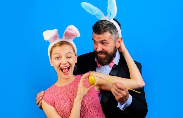 Семья празднует пасху и раскрашивает яйцо. пара в ушах зайчика с пасхальным яйцом.