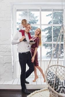 Семья празднует рождество и новый год. мама, отец и сын обнимаются, семейный праздник
