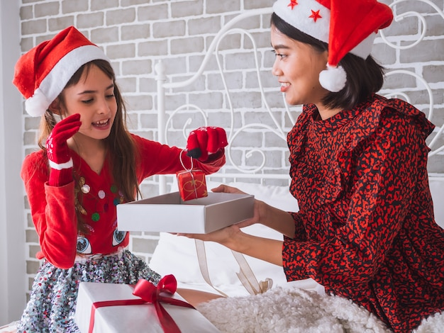 The family celebrates christmas by giving their daughter a gift