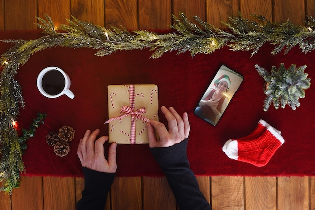 Family celebrates virtual christmas from afar by communicating via video conference and opening gifts at home