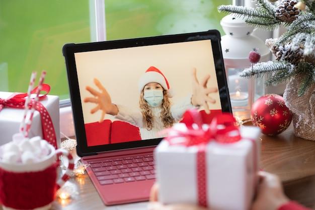 検疫のビデオチャットでオンラインでクリスマス休暇を祝う家族。封鎖の家の概念。パンデミックコロナウイルスcovid19中のクリスマスパーティー
