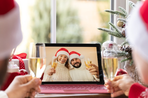 Family celebrating christmas holiday online by video chat in quarantine. lockdown stay home concept. xmas party during pandemic coronavirus covid 19