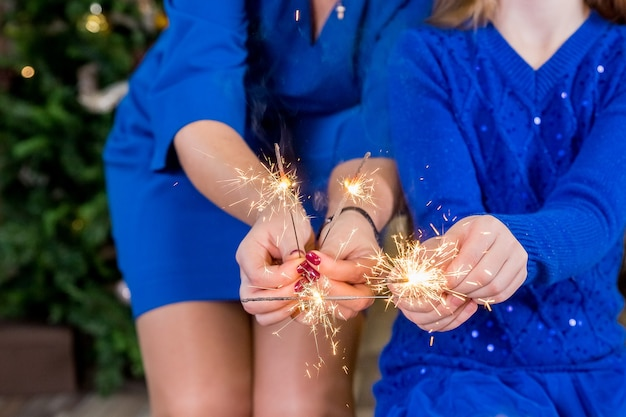 Family celebrating christmas holidays, party people holding sparklers, festive lights for new year or birthday