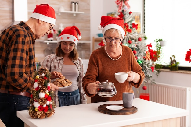Family celebrating christmas season together in xmas decorated culinary kitchen
