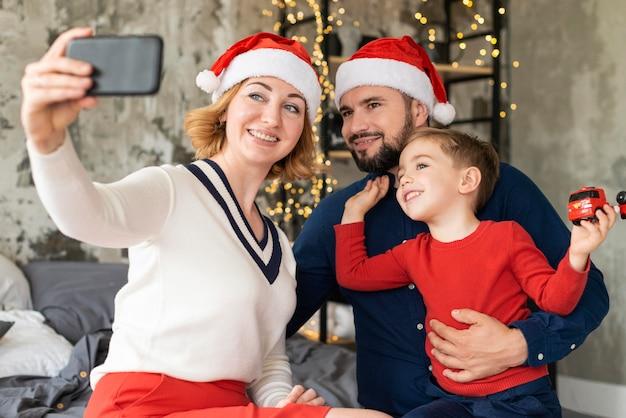 Семья празднует рождество вместе с селфи