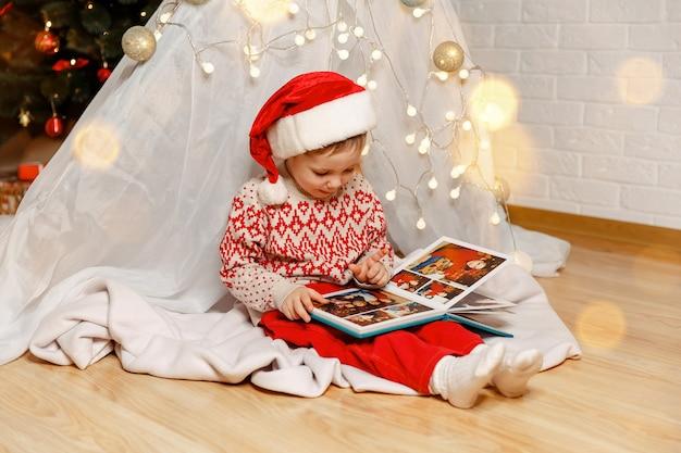 Семья празднует праздники, счастливый мальчик смотрит на семейный альбом