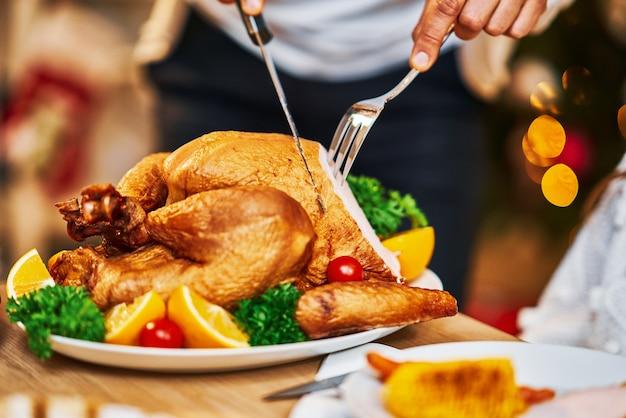感謝祭を祝う家族。テーブルとディッシュに焦点を当てる