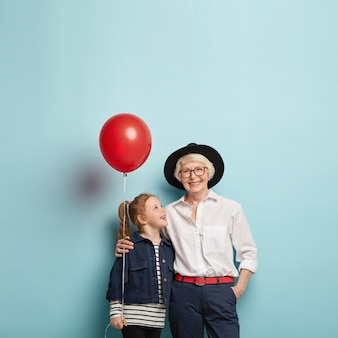 Family celebration concept. cute red haired girl congratulates mature granny with mothers day, holds red air balloon, embrace together, isolated over blue wall with blank space.