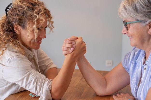가족의 도전, 곱슬곱슬한 금발의 딸, 그리고 노부부가 집에서 얼굴을 맞대고 탁자 위에서 팔씨름을 하는 농담