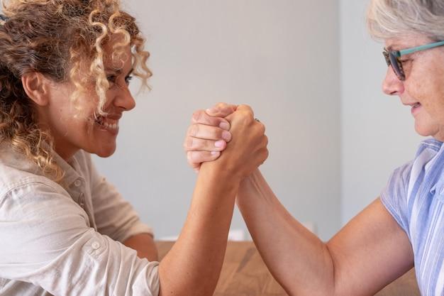 Семейный вызов, кудрявая блондинка дочь и старшая мать шутят по армрестлингу на столе дома лицом к лицу