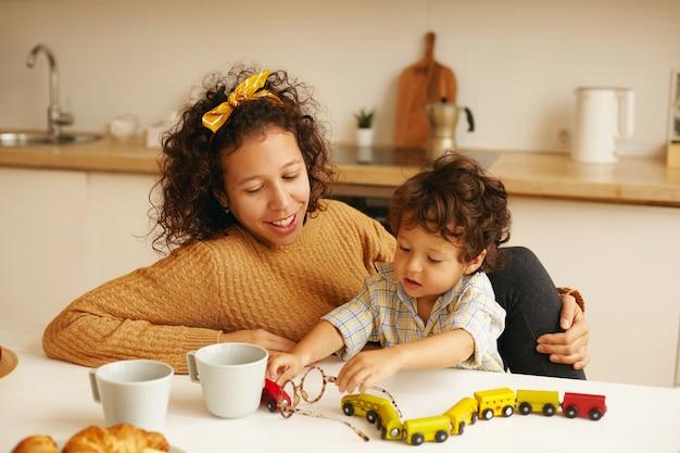 가족, 육아, 학습, 발달 및 미세 운동 기술 개념. 잘 생긴 아기 아들이 그녀의 옆에 앉아 장난감 철도를 가지고 노는 동안 부엌에서 커피를 마시는 돌보는 젊은 히스패닉 여자
