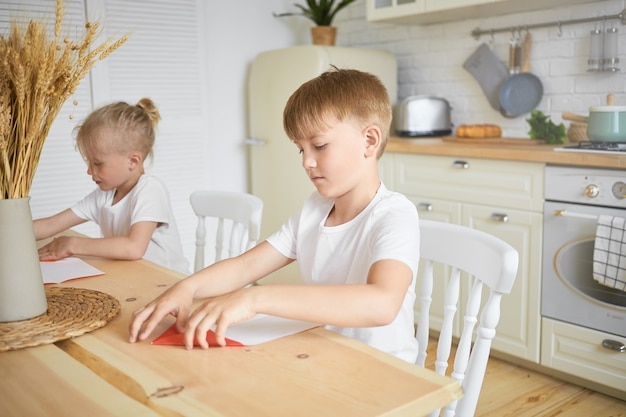 Family and childhood concept. portrait of two male siblings of school age sitting together at table in kitchen: blonde boy doing homework while his elder brother making origami in foreground