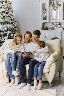 Family, childhood, holidays and people - smiling mother, father and little kids reading book over lights background