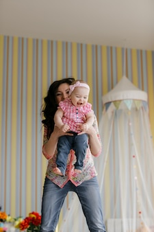 Family, childhood and parenthood concept. happy little baby learning to walk with mother help at home