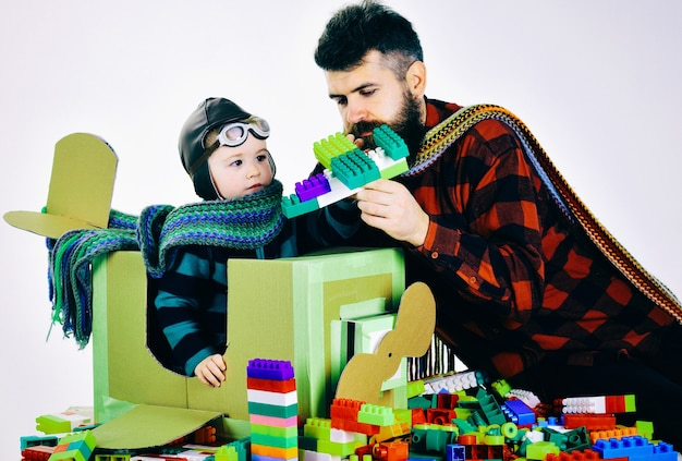 Family childhood son and dad play with colorful plastic blocks father and kid spend time together