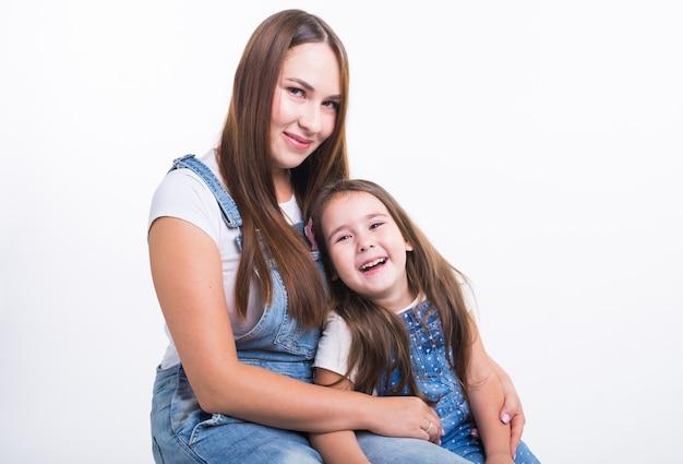 家族、子供、母性の概念-若い母親と彼女の若い娘は白い壁に孤立して一緒に時間を過ごします。