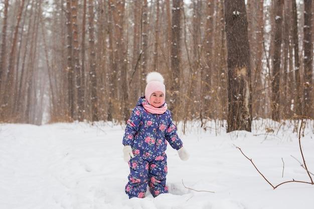 家族、子供、自然のコンセプト-美しい小さな子供の女の子はウィンターパークで楽しんでいます
