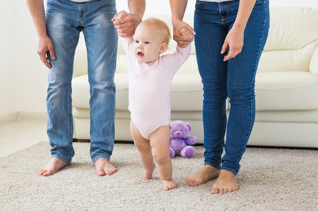 家族、子供、親の概念-女の赤ちゃんに歩くことを教える親。