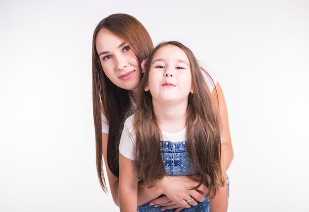 가족, 어린이, 부모 개념-흰색 표면에 그녀의 작은 귀여운 아이와 젊은 여자
