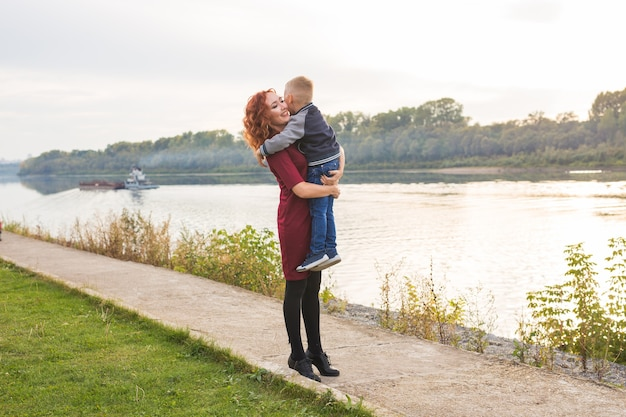 Family and children concept - redhead woman holding her son over water background.