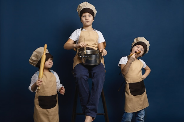 Famiglia, bambini e concetto di cucina. un ritratto in studio isolato di tre fratelli di bambini caucasici in posa in uniforme da chef, tenendo vari utensili da cucina, preparando insieme la zuppa o facendo la pizza