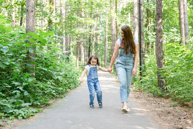 Family children and nature concept portrait of attractive woman and little child girl walking