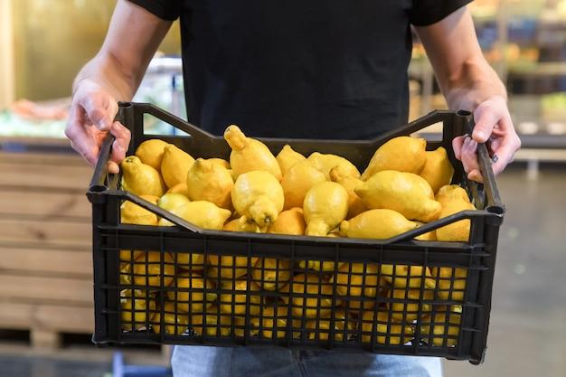 슈퍼마켓에서 레몬과 과일을 선택하는 가족