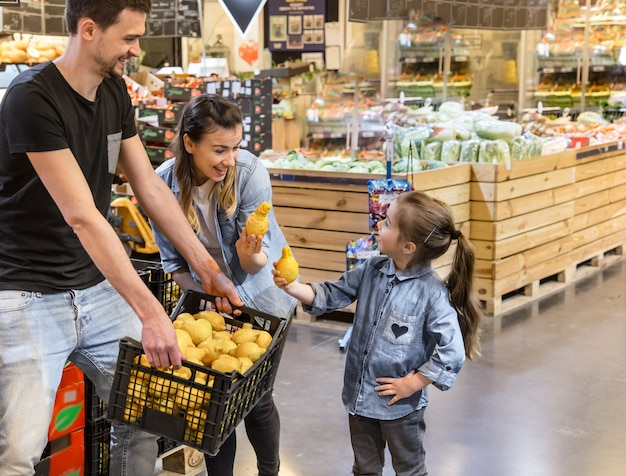 Family choosing lemons and fruits in supermarket