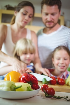Family chopping vegetables in the kitchen