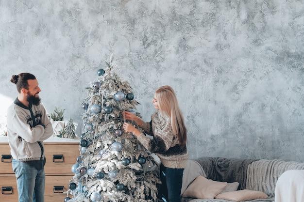 가족 크리스마스 축하. 집에서 전나무 트리 장식 즐기는 행복 한 커플