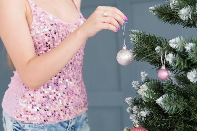 家族のクリスマスの家の装飾の伝統。モミの木に銀色のキラキラボールをぶら下げている女性。休日のお祭りの装飾と装飾の概念。