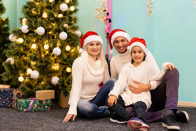 Семья, рождество, рождество, зима, счастье и люди концепция - улыбающаяся семья в шляпах санта-помощника с множеством подарочных коробок и бенгальских огней
