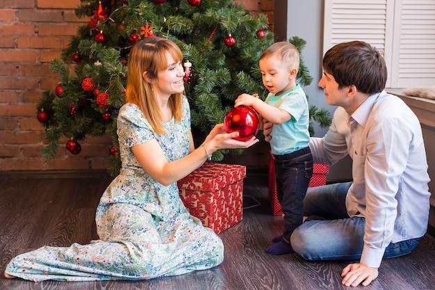 家族、クリスマス、クリスマス、冬、幸福と人々の概念-クリスマスツリーの下に座っている男の子と笑顔の家族。