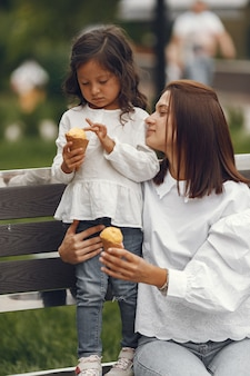 Family in a city. little girl eats ice cream. mother with daughter sitting on a bench.