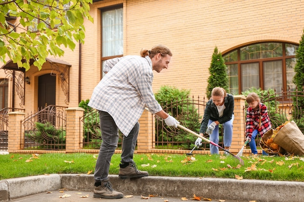 屋外で紅葉を掃除する家族