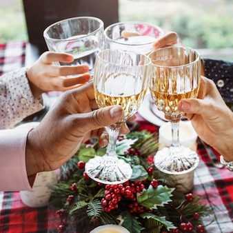 Family clinking with glasses at christmas dinner table