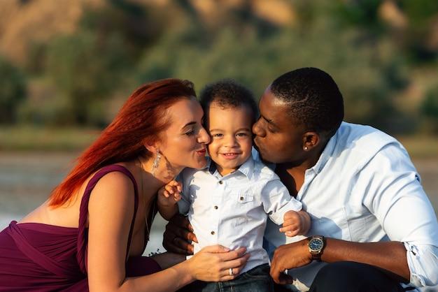 Семейная близость. счастливые дни наполнены весельем. родители с сыном на пляже.